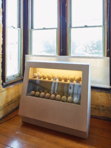David Ireland, Dumbball Box, 1983; Wood, plastic laminate, glass, light bulb, cement