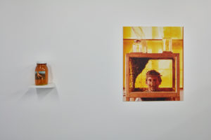 (Left) Mark Thompson, Resting Hand, 1976–1977, Photographic color label on glass jar, honey, shelf.  (Right) Mark Thompson A House Divided, 1989 Interior view from the series of meditations of immersing my head within the honeybee hive, Chromogenic print