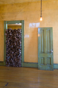 David Ireland, 500 Capp Street (interior view with logs in doorway), 1987. Wood, 80 x 33 x 15 inches. Remade for the exhibition Amulet or He calls it chaos, 2019.